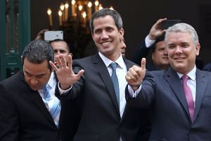 Guaido (centre) and Colombiam President Ivan Duque gesture after a meeting in Bogota, Colombia.