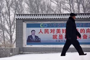 A photograph of President Xi Jinping seen on a propaganda billboard in China's northern Hebei province. A propaganda app that teaches