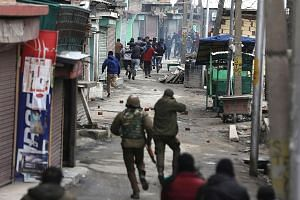 Indian police officers chasing Kashmiri Muslim protesters during clashes that erupted after an anti-terror agency raided the house of top separatist leader Mohammad Yasin Malik in Srinagar yesterday.