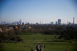 People walking across Primrose Hill during sunny weather in London, Britain on Feb 24, 2019.