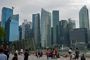 The Marina Bay waterfront promenade with the skyline of Singapore's central business district in the background.