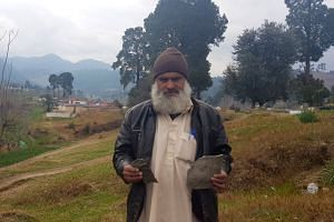 Fida Hussain, 46, holds what he believes to be fragments of a payload released by the Indian military in Jaba village, Pakistan.