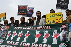Pakistani activists carry placards during a peace rally in Islamabad on March 1, 2019.
