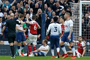 Referee Anthony Taylor gives a penalty after Tottenham's Harry Kane (centre) is fouled by Arsenal's Shkodran Mustafi (right).