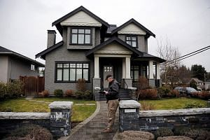 A member of a private security firm outside the family home of Huawei's chief financial officer Meng Wanzhou, in Vancouver, Canada, in January this year. Meng, the daughter of company founder Ren Zhengfei, was detained in December at Washington's req