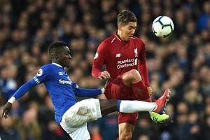 Everton's Senegalese midfielder Idrissa Gueye (left) vies with Liverpool's Brazilian midfielder Roberto Firmino during the English Premier League football match between Everton and Liverpool at Goodison Park in Liverpool, north west England on March