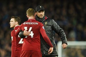 Liverpool's English midfielder Jordan Henderson (left) is embraced by Liverpool's German manager Jurgen Klopp after drawing the English Premier League football match between Everton and Liverpool at Goodison Park in Liverpool, north west England on M