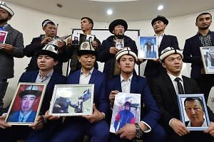 Citizens of ex-Soviet Kyrgyzstan holding portraits of their relatives - who they fear are being held in re-education camps in China's Xinjiang region - at a press conference in the Kyrgyzstan capital Bishkek last November, as they appealed to the cou