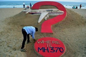 Indian sand artist Sudarsan Pattnaik creating a sculpture of missing Malaysia Airlines flight MH370 on Puri beach in eastern Odisha state on March 7, 2015.