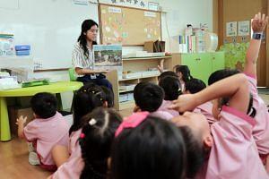 Teacher Chng Shu Min, 25, at St James' Church Kindergarten (Leedon campus) uses The Straits Times to teach children current affairs.