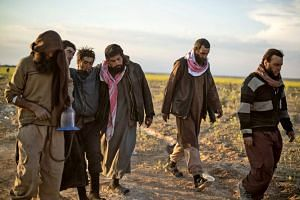 Men suspected of being ISIS fighters walk towards a screening point for new arrivals run by US-backed Syrian Democratic Forces.