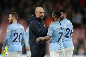 City manager Pep Guardiola celebrates with players after the team defeated Bournemouth.