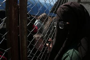 A woman looks through a chain linked fence at al-Hol displacement camp.