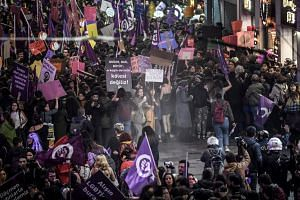 Turkish anti-riot police officers use rubber bullets as they push back women during a rally marking International Women's Day in Istanbul.