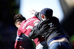 Aston Villa midfielder Jack Grealish was in the Birmingham penalty area in the 10th minute when a man ran onto the field and threw a punch from behind at the Villa captain.