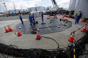 Workers building a storage tank (above) for radioactive water and doing decontamination work (left) at Tokyo Electric Power's tsunami-crippled nuclear power plant. Fukushima wants to be the domestic leader in robotics and drones, as well as in sustai