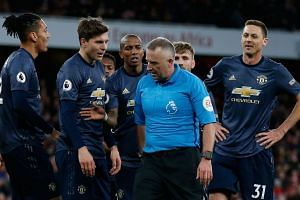 Manchester United players crowd around referee Jonathan Moss after Moss gave a penalty to Arsenal.
