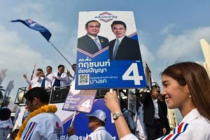 A Phalang Pracharat party supporter displays an electoral placard of Thai Prime Minister Prayut Chan-O-Cha in Bangkok.