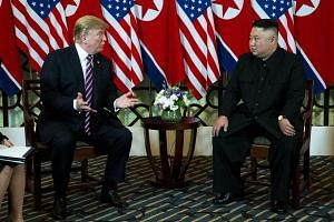 US President Donald Trump (left) speaking to North Korean leader Kim Jong Un during their summit in Hanoi, Vietnam, on Feb 27, 2019.