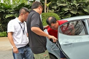 Murder suspect Leslie Khoo Kwee Hock (in red) was taken to Gardens by the Bay, the scene of the alleged crime, accompanied by plain-clothes officers.