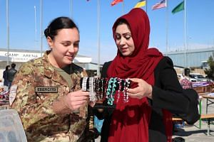 An Afghan woman displays handmade items at an exhibition organised by Italian soldiers of Nato Resolute Support Mission in Herat, Afghanistan, March 10, 2019.