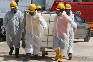 Emergency personnel wearing protective suits prepare materials for the clean up of Sungai Kim Kim river in Pasir Gudang, southern Malaysia, on March 14, 2019.