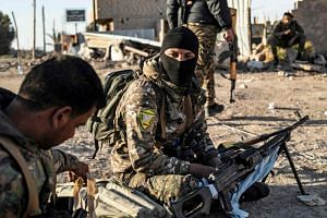 Fighters with the Syrian Democratic Forces pictured in the town of Baghouz, in the eastern Syrian province of Deir Ezzor, on March 12, 2019.