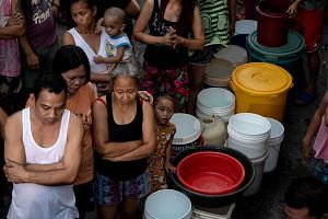Residents of Addition Hills in Madaluyong City, Manila, queue to receive water distributed from water tank trucks and fire trucks on March 15, 2019.