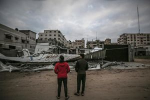Palestinians inspect a destroyed Hamas site after an Israeli airstrike in Gaza City, on March 15, 2019.