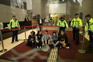 Protesters from Demosisto and Lingnan University surrounded by security after storming Hong Kong government headquarters over a proposal to extradite fugitives to mainland China, on March 15, 2019.