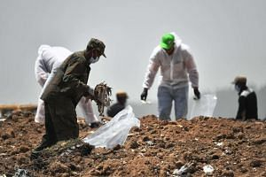 Forensics experts comb through the dirt for debris at the crash site of the Ethiopian Airlines operated Boeing 737 Max aircraft, at Hama Quntushele village in Oromia region, on March 14, 2019.
