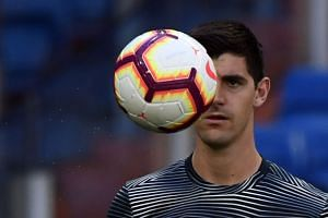 Courtois eyes the ball as he warms up before a match.