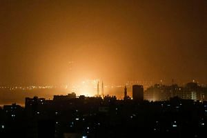 The sky above the Gaza Strip glows orange during an Israeli air strike in Gaza city late on March 14, 2019.
