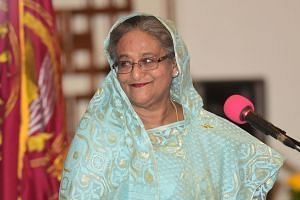 Sheikh Hasina smiles as she is sworn in for her fourth spell as Bangladesh's prime minister.