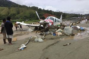 A damaged aircraft is seen at a silt-covered airstrip following flash floods in Sentani near the provincial capital of Jayapura, Indonesia's eastern Papua province, on March 17, 2019.