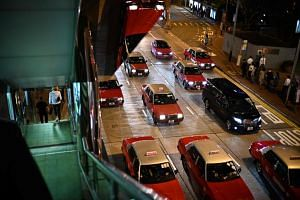Local red taxis are driven past a stairway that leads down from a walkway between shopping malls in Hong Kong on Feb 28, 2019.