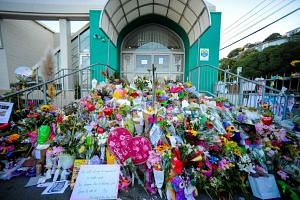 Flowers left by residents are seen at a memorial site for victims of the Christchurch mosque attacks at an Islamic Center in Kilbirnie, Wellington on March 19, 2019.