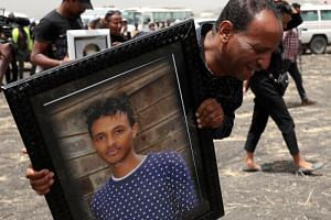 A relative carries a portrait of Ethiopian Airlines pilot Yared Getachew as he mourns at the scene of the Ethiopian Airlines Flight ET 302 plane crash, near the town Bishoftu, Ethiopia on March 14, 2019.