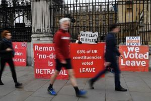 Pro-Brexit campaigners outside Parliament in London yesterday. British Prime Minister Theresa May has written to European Council president Donald Tusk to request a delay to Brexit until June 30.