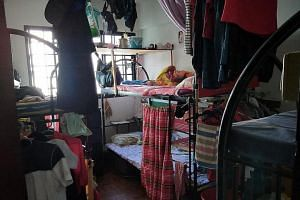 Clothes hanging haphazardly from the beds and ceiling.