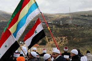 Members of the Druze community hold Syrian and Druze flags during a rally marking the anniversary of Israel's annexation of the Golan Heights in the Druze village of Majdal Shams, in the Israeli-occupied Golan Heights, on Feb 14, 2019.