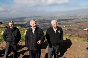 A photo taken on March 11 showing (from left) US Senator Lindsey Graham, Israeli Prime Minister Benjamin Netanyahu and US Ambassador to Israel David Friedman visiting the border line between Syria and the Israeli-annexed Golan Heights. Mr Netanyahu y