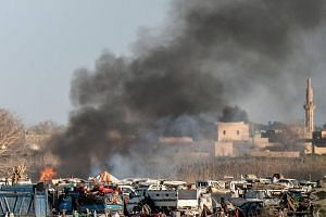 Smoke rising from a makeshift camp for Islamic State members in Baghouz, Syria, on March 9, 2019.