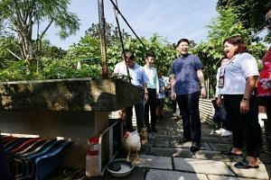Senior Minister of State for Trade and Industry Chee Hong Tat (centre) at a community garden as part of a tour of Ang Mo Kio yesterday.