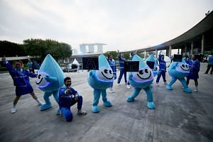Water Wally parade participants getting ready for the GoBlue4SG night carnival at Marina Barrage yesterday to mark World Water Day. A record 30 landmarks and buildings, including Marina Bay Sands, turned blue yesterday to support water conservation.