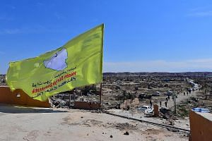Left: The Syrian Democratic Forces hoisted their yellow flag atop a bullet-riddled building in the Syrian village of Baghuz yesterday, proclaiming the