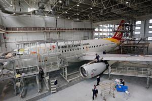 Employees work on an Airbus A319 aircraft of Beijing Capital Airlines at an aircraft maintenance base in Yichang, Hubei province, China, on March 15, 2019.