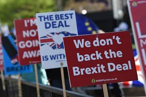 Anti-Brexit placards are lined up on railings outside the Houses of Parliament in London on March 25, 2019.