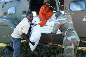 Workers offload food aid from a South African National Defence Force helicopter in the aftermath of Cyclone Idai in Buzi, near Beira, Mozambique on March 25, 2019.