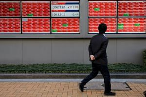 A man looks at an electronic board showing the Nikkei stock index outside a brokerage in Tokyo.